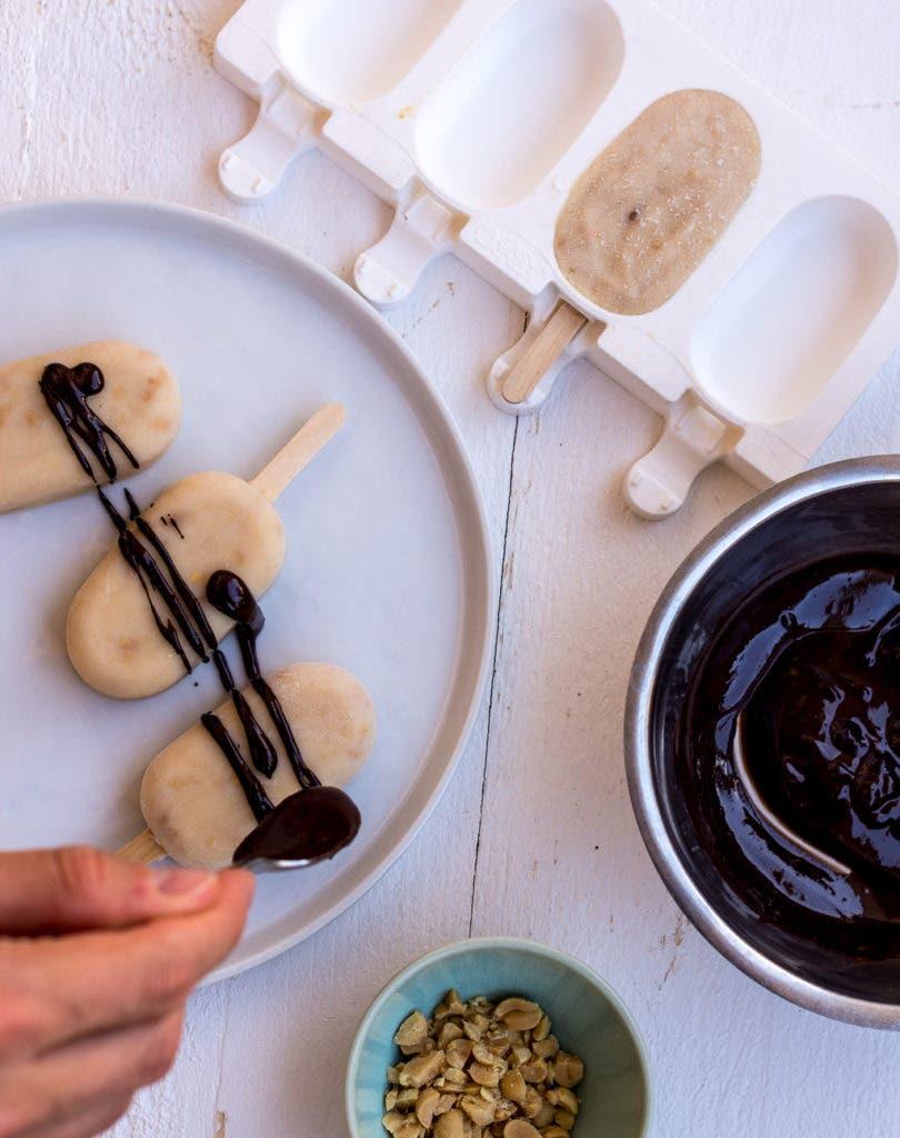 Topshot von selbstgemachtem Erdnusseis, das mit geschmolzener Schokolade verziert wird.
