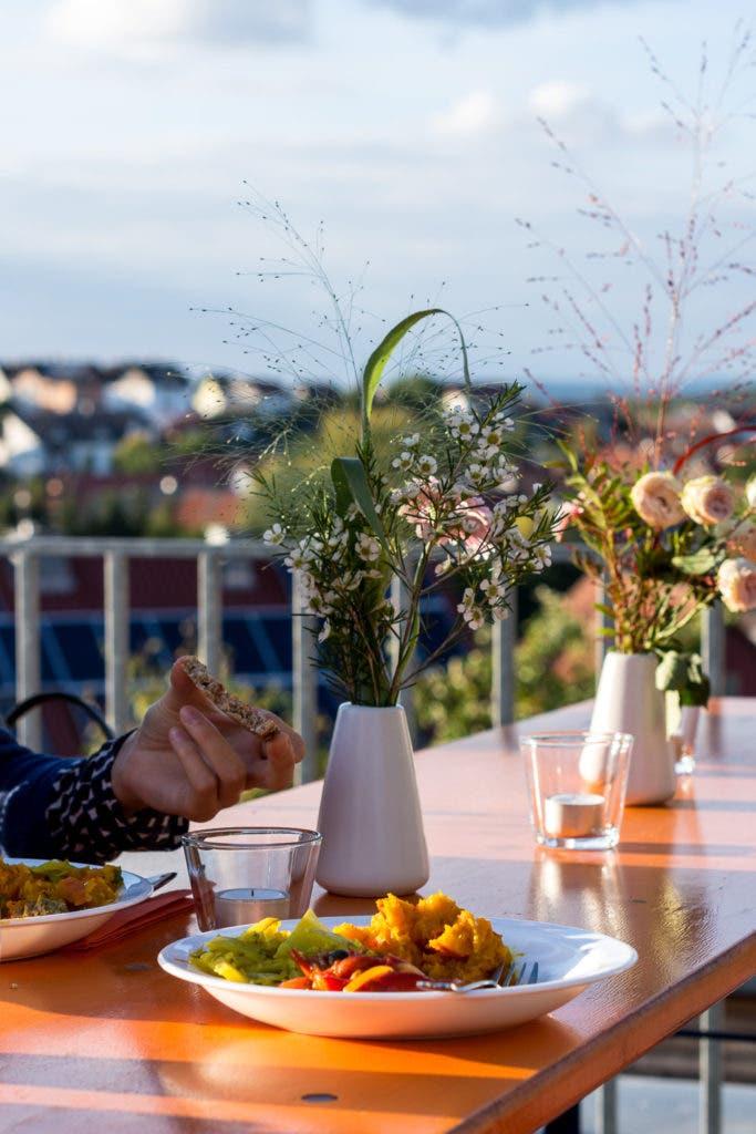 Tisch auf Terrasse mit Blumenvasen und gefüllten Tellern