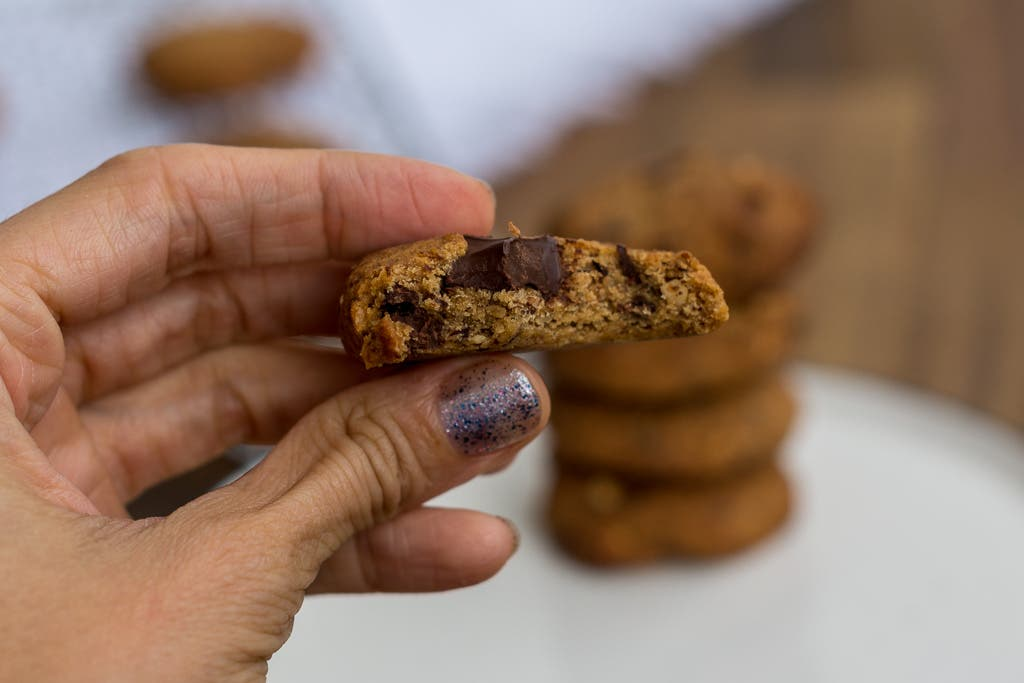 angebissener Schokoladenkeks in Kamera gehalten