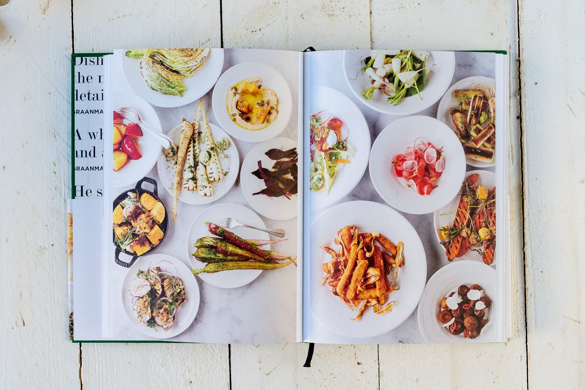 Aufgeschlagenes Kochbuch mit Fotos von Tellern und Rezepten auf weißem Untergrund.