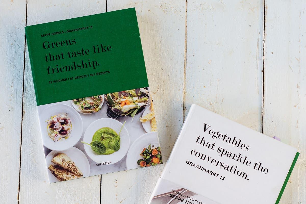 """Kochbücher """"Greens that taste like friendship"""" und """"vegetables that sparkle the conversation"""" auf weißem Untergrund."""