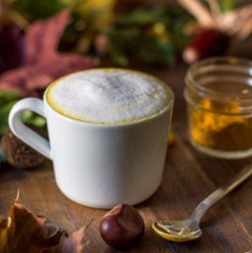 Tasse mit Kurkuma Latte und Milchschaum vor herbstlichen Blättern