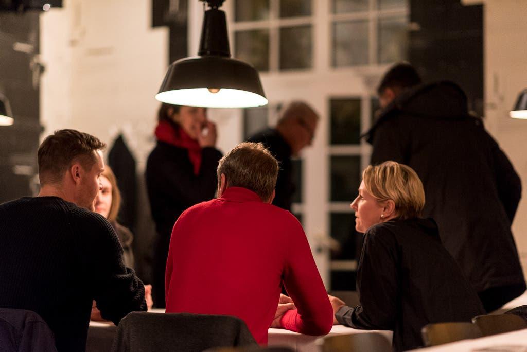 Personengruppe von hinten fotografiert, sitzt an einem Tisch und unterhält sich.