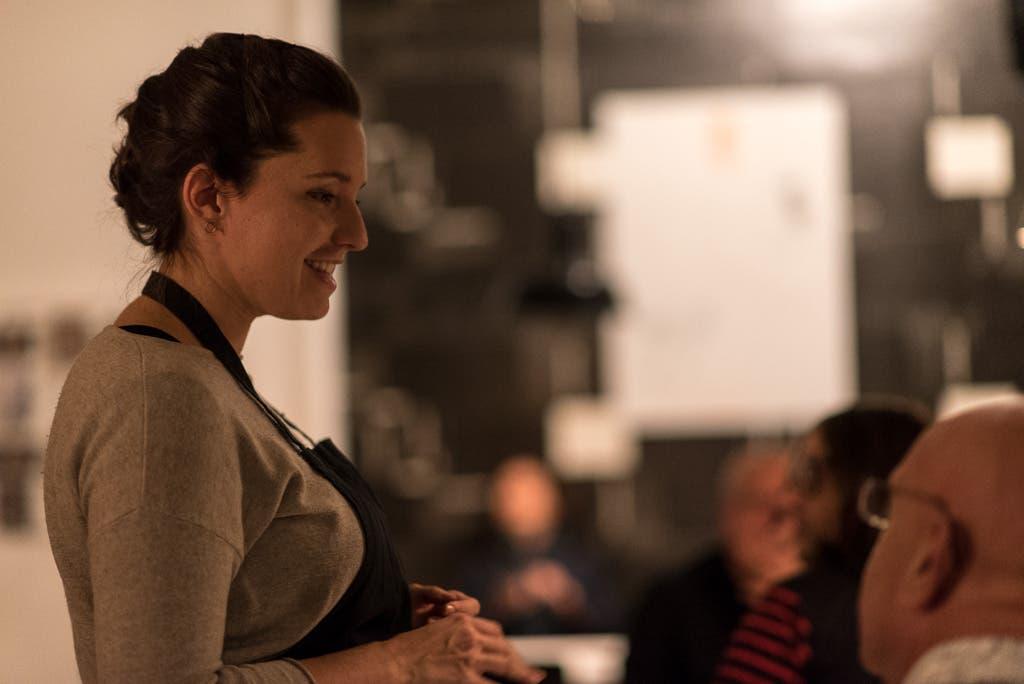 Frau in Kochschürze unterhält sich mit Personen in einem Restaurant.