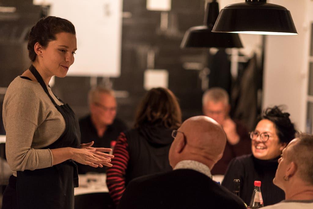 Frau trägt eine Kochschürze und spricht mit Personen an einem Tisch.