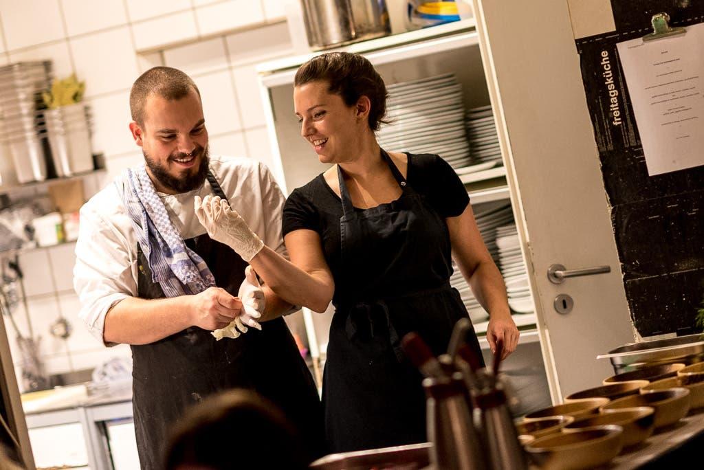 Mann und Frau stehen lachend in einer Gastroküche.
