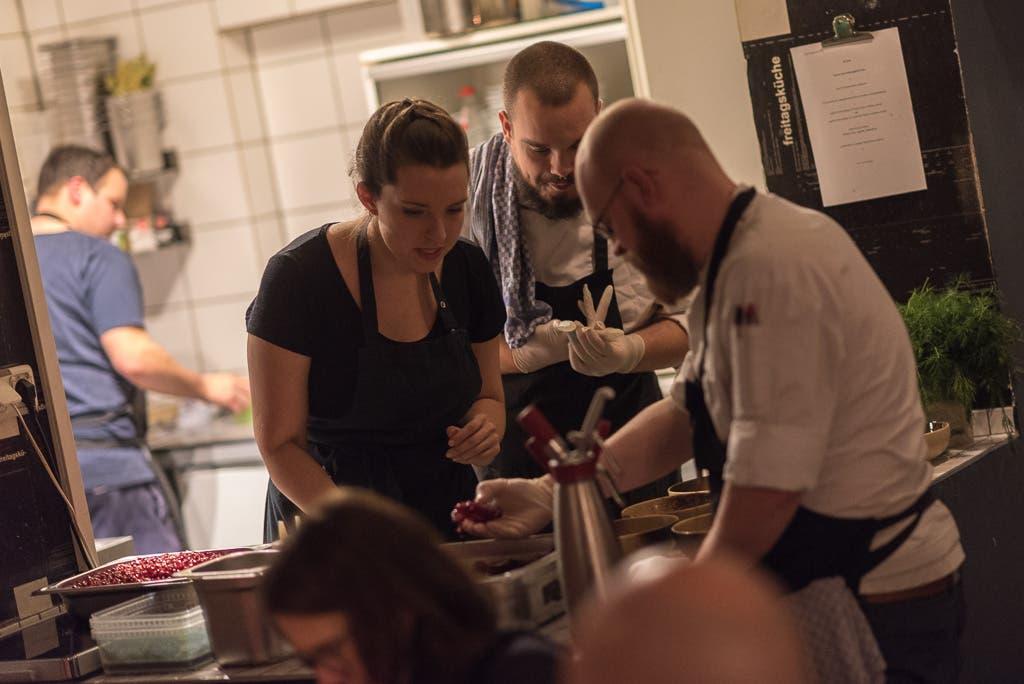 Frau und zwei Männer beugen sich über einen Tisch mit Tellern und Schüsseln.