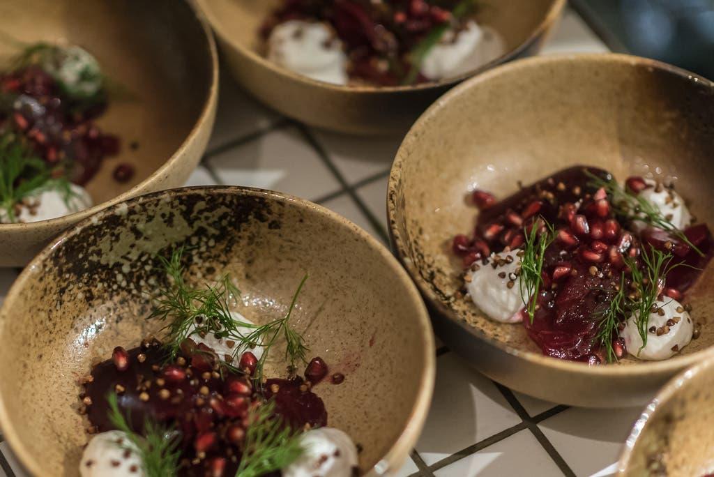 Mehrere Teller mit Rote Bete, Dill und Granatapfelkernen.