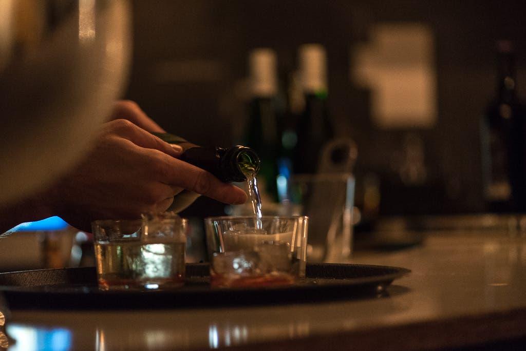 Hand gießt ein klares Getränk in ein Glas.