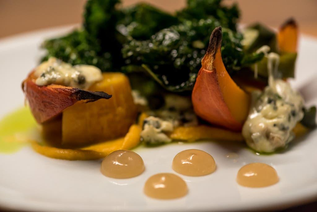 Close up von geschmortem Gemüse mit Sauce auf einem weißen Teller