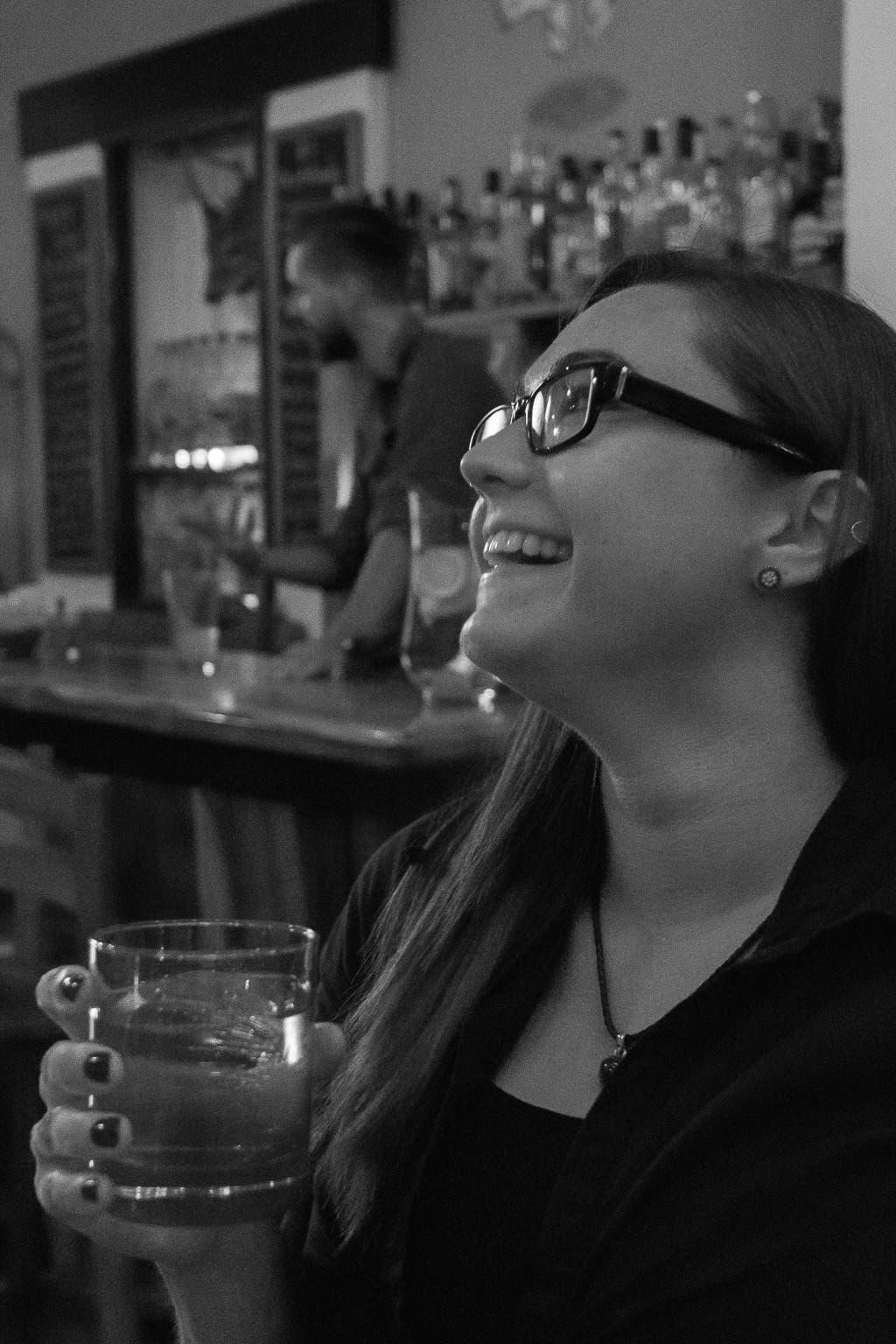 Seitliche Ansicht von lachender Frau mit Glas in der Hand