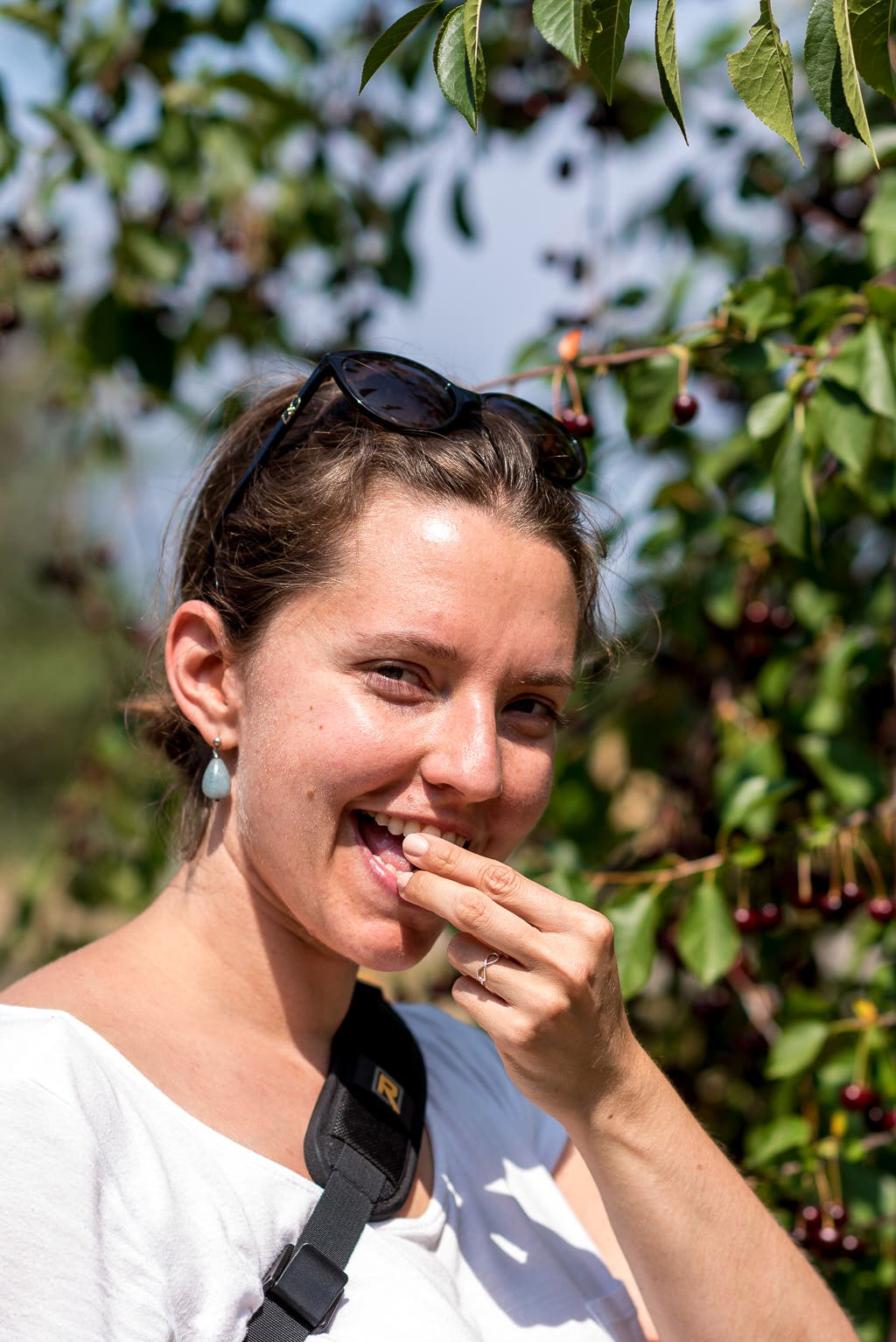 lachende Frau beim Kirschenessen