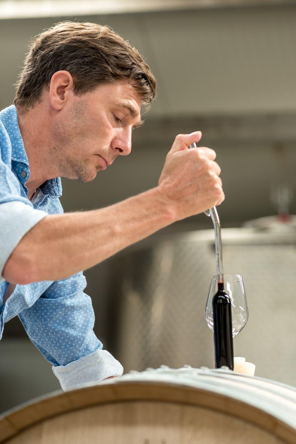 Mann beim Einfüllen von Rotwein