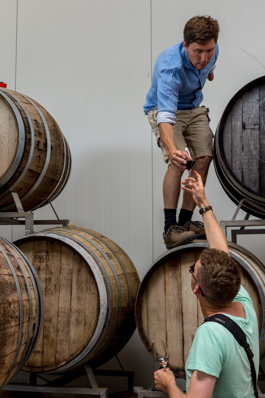 Mann reicht anderem Mann von Weinfässern gefülltes Rotweinglas