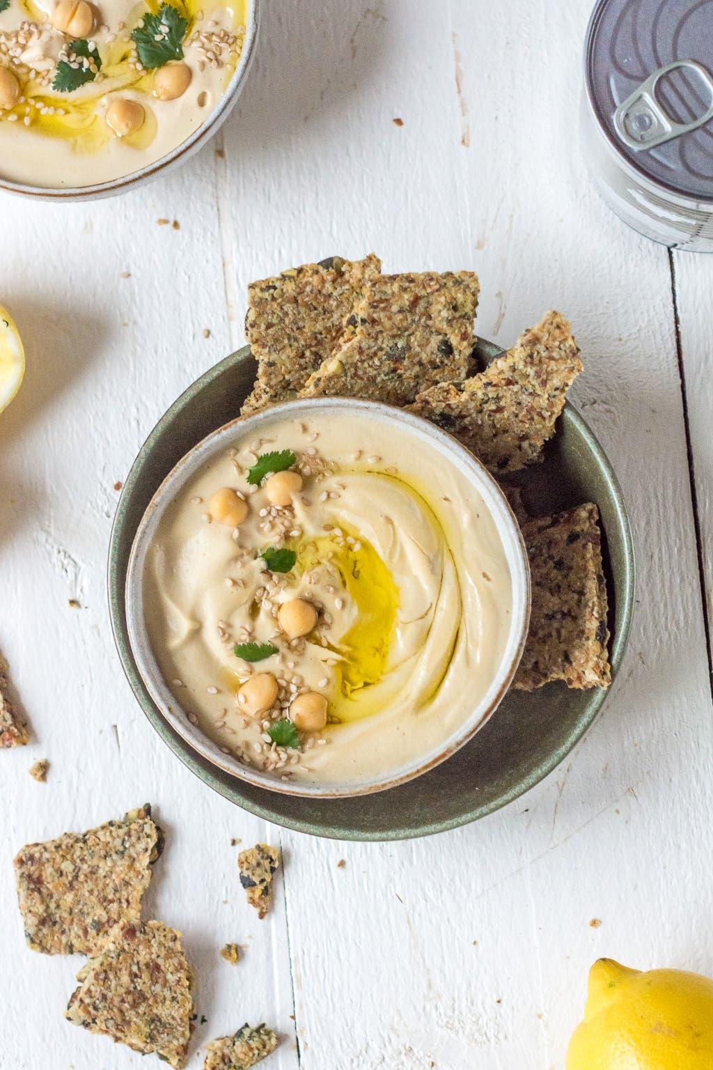 Topshot von Hummus in Schale mit Knäckebrot angerichtet
