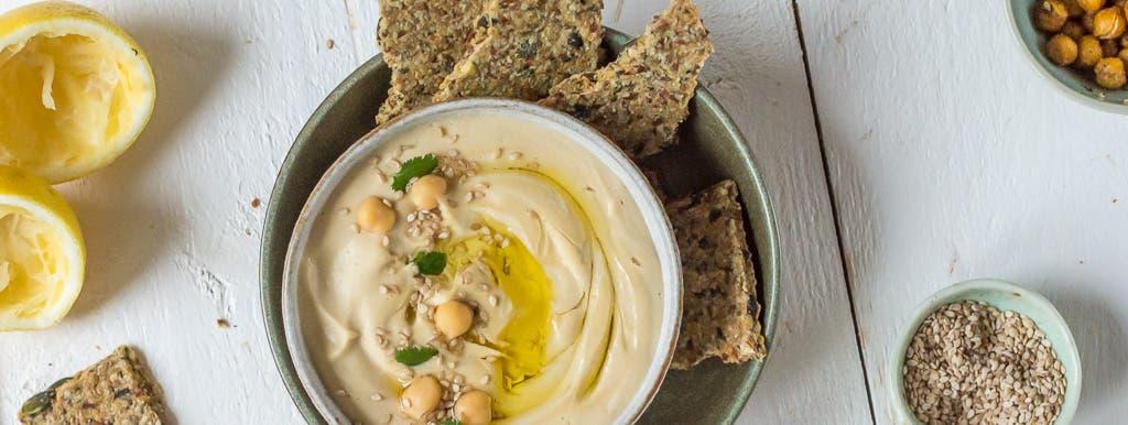 Topshot von Hummus in einer Schale mit Kichererbsen, Knäckebrot, Zitronen und Kernen auf weißem Holzuntergrund dekoriert