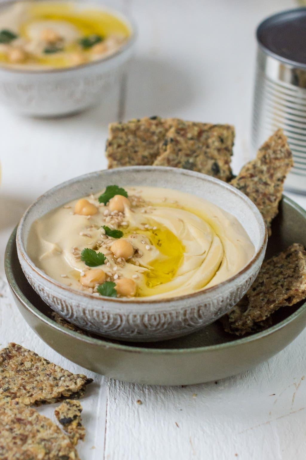 Hummus in Schüssel mit Kichererbsen und Knäckebrot dekoriert