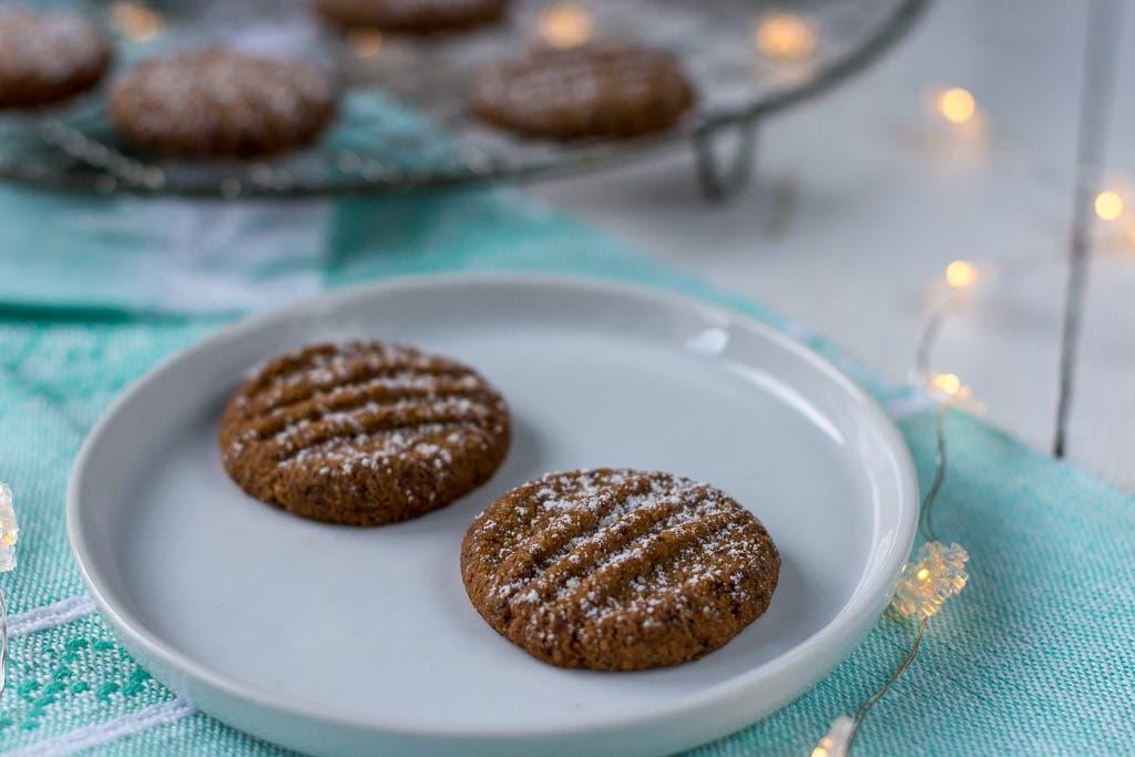 zwei Kekse auf weißem Teller liegend mit Lichterkette und blauem Tuch
