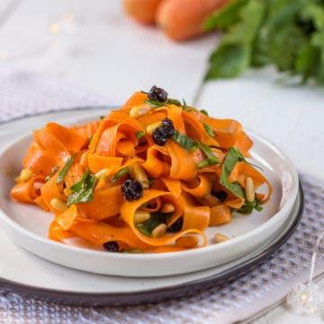 Karottenalat mit Rosinen und Curry auf hellem Teller angerichtet