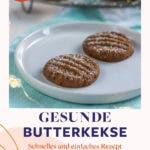 Zwei Kekse mit Puderzucker bestreut auf weißem Teller mit Lichterkette.
