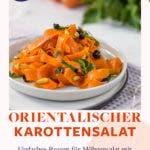 Karottensalat mit Rosinen und Curry auf weißen Teller angerichtet