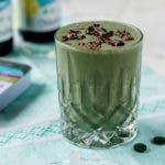 grüner Smoothie im Glas mit Kakaonibs bestreut