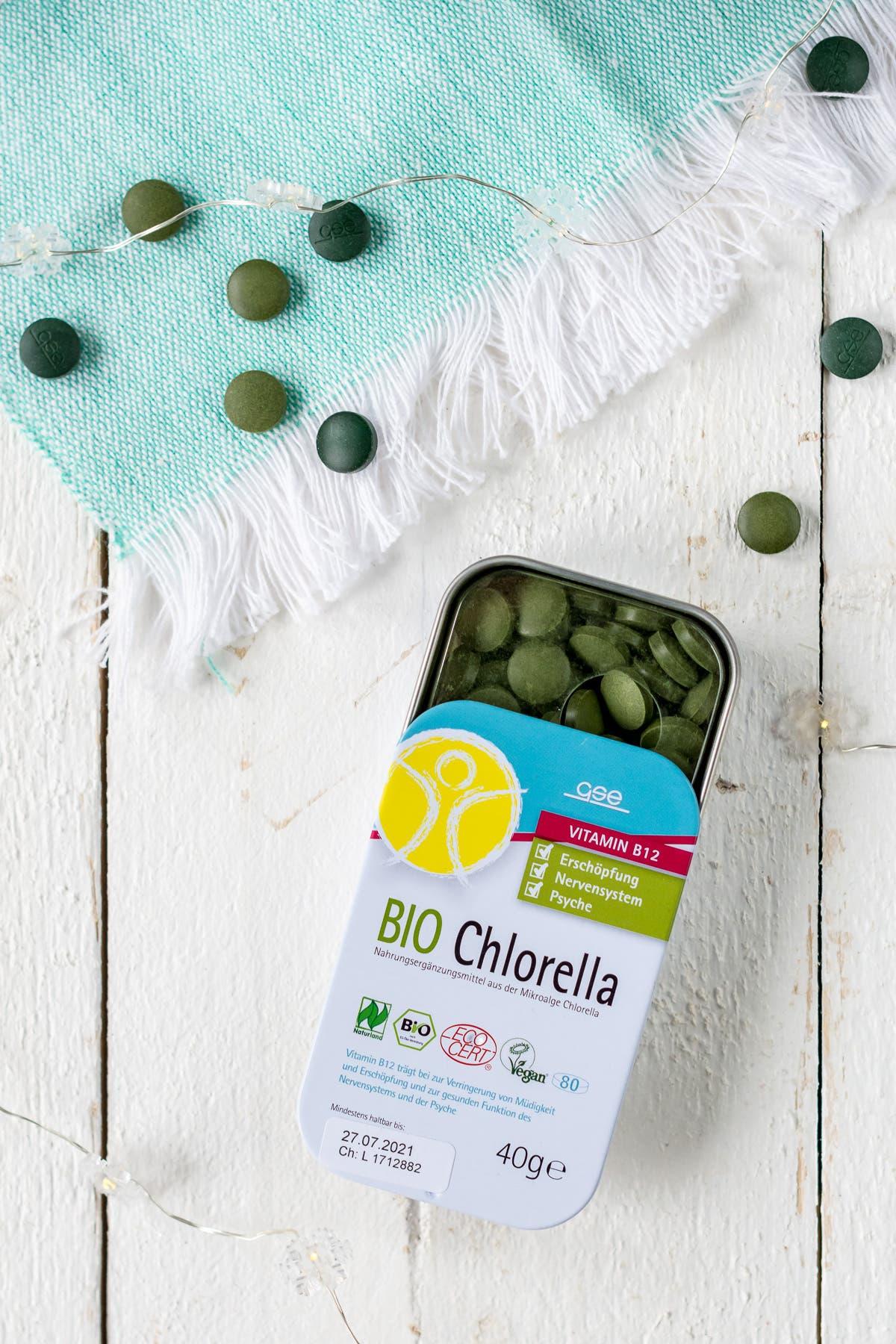 Bio Chlorella Tabletten in Dose auf weißem Holzuntergrund