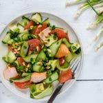 Topshot von frischem Gurkensalat mit Grapefruit auf Teller