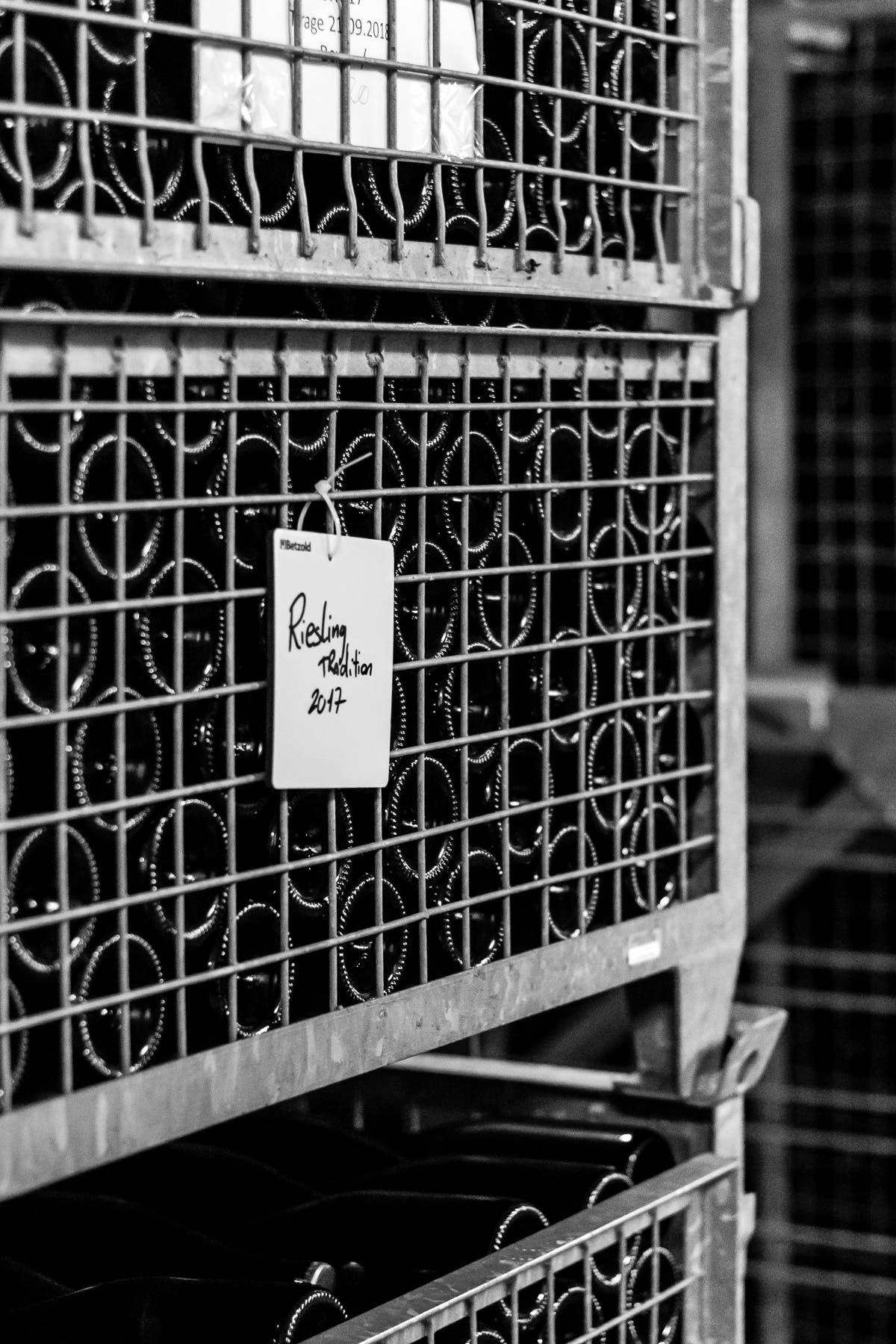 Gitterregal mit liegend gelagerten Glasflaschen.