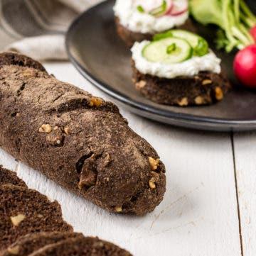 Dunkles Walnussbaguette vor Teller mit belegten Brotscheiben