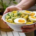 Kartoffelsalat mit Eierhälften und Petersilie in Schüssel
