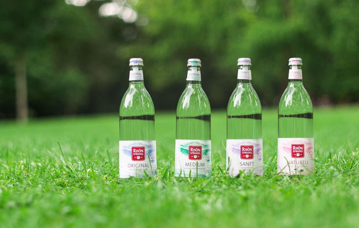Vier Glasflaschen von RhoenSprudel nebeneinander im Gras stehend