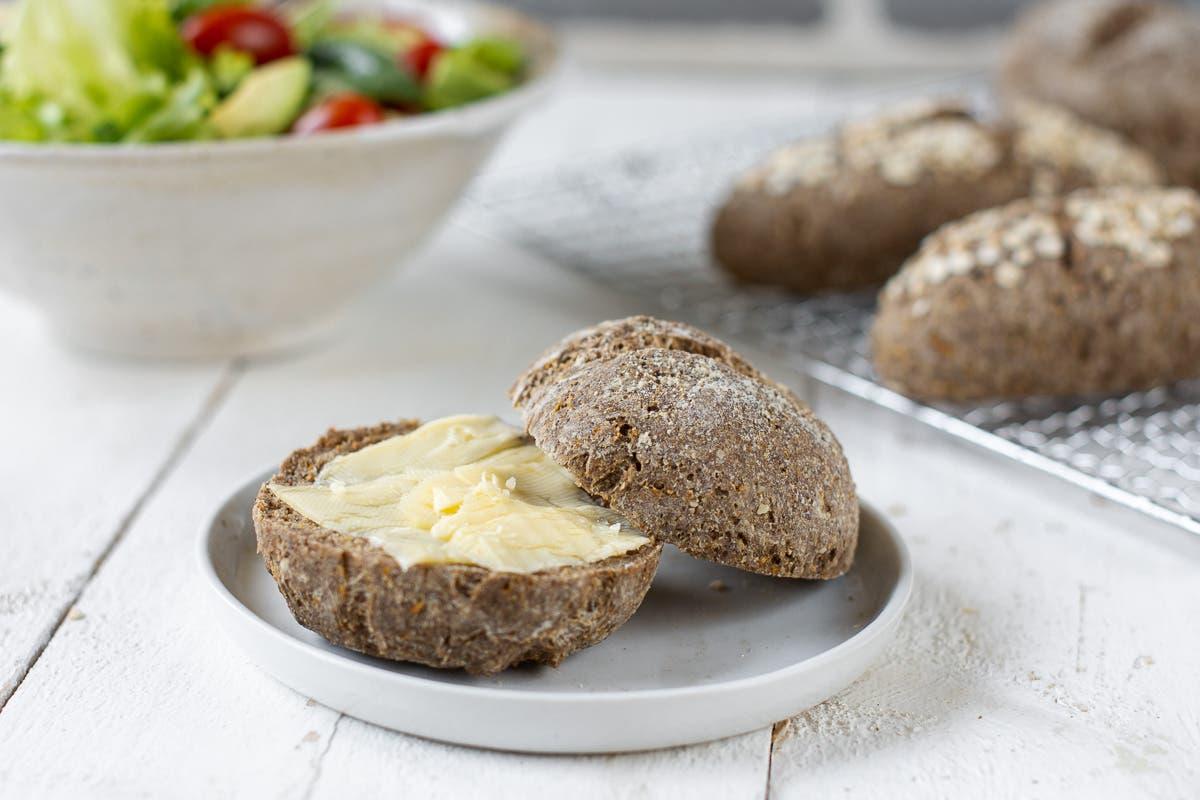 Ein weißer Teller mit einem aufgeschnittenem Brötchen mit Butter bestrichen.