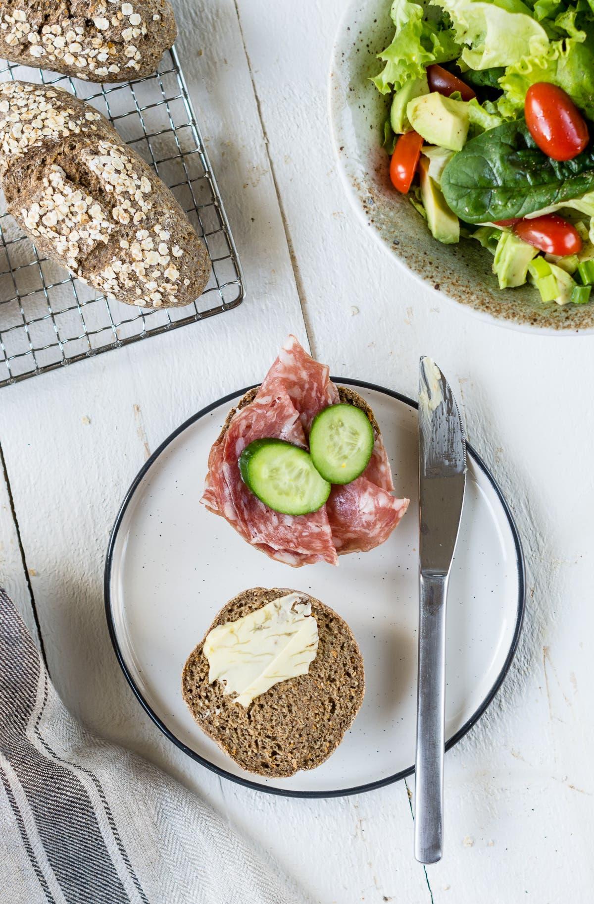 Top Shot von aufgeschnittenem Brötchen belegt mit Butter und Salami auf gedecktem Tisch