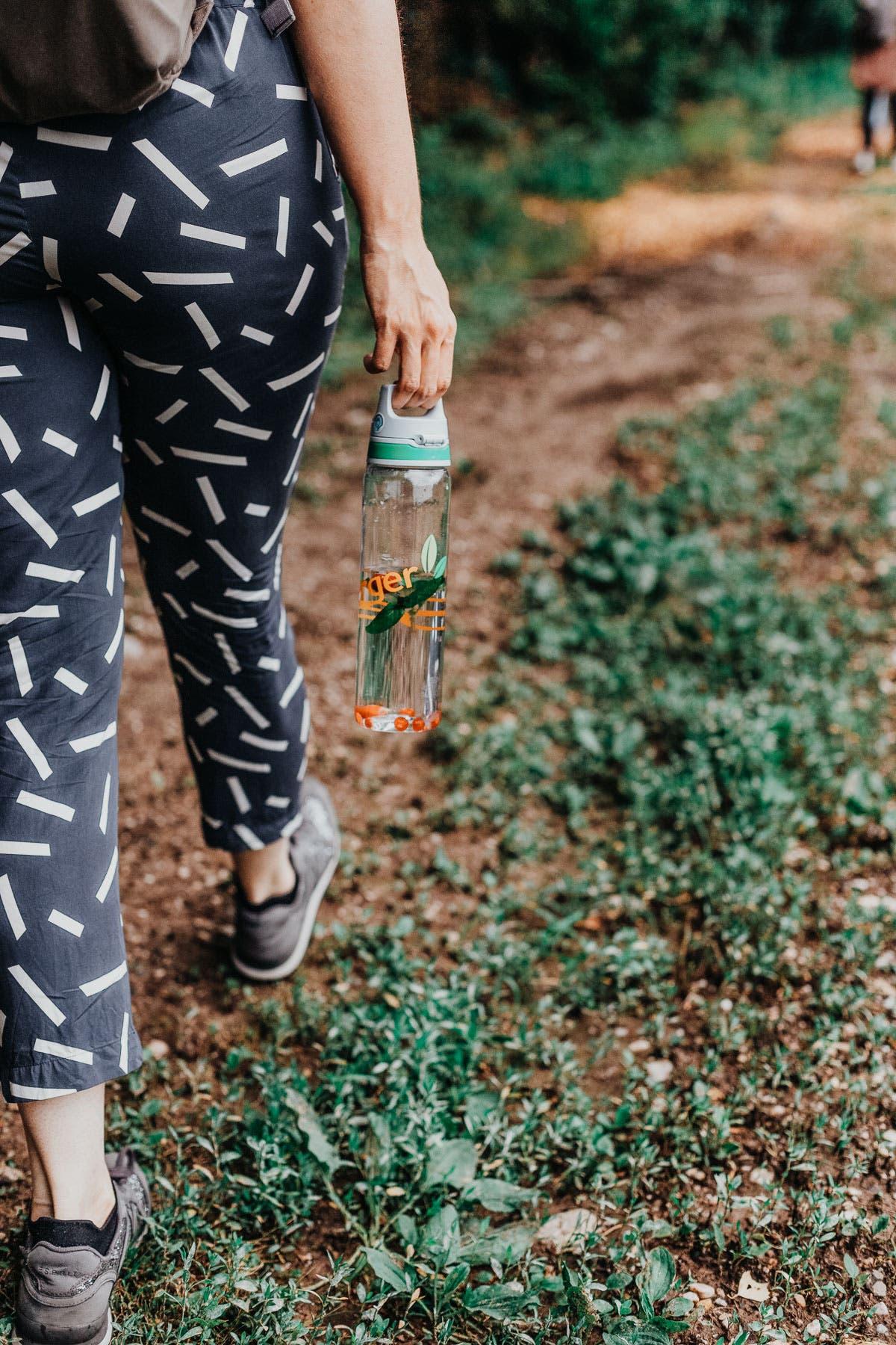 Rückansicht von Person die eine Flasche in der Hand hält und auf einem Waldweg geht.