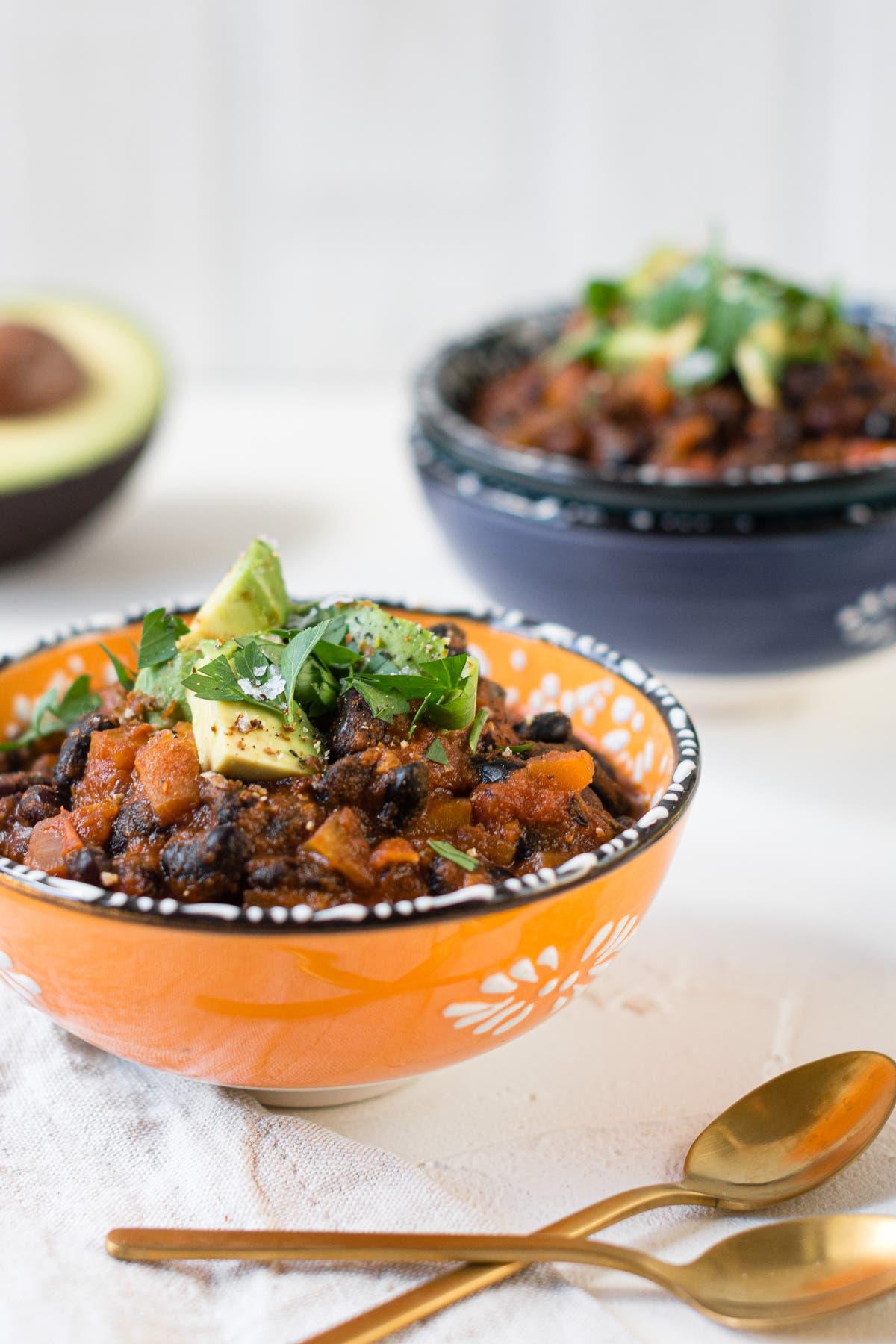 Hochformat von zwei Schüsseln gefüllt mit Chili sin Carne getoppt mit Petersilie und Avocado