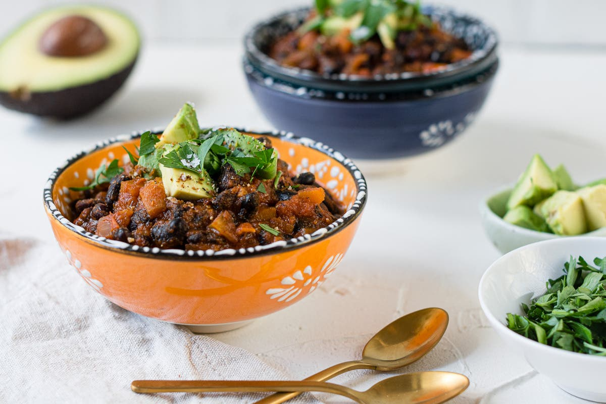 seitliche Ansicht von Chili in orangefarbener Schale, mit Petersilie und Avocado dekoriert