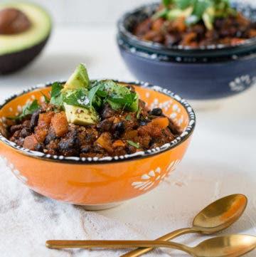 Zwei Schüsseln gefüllt mit Chili sin Carne und getoppt mit Petersilie und Avocado