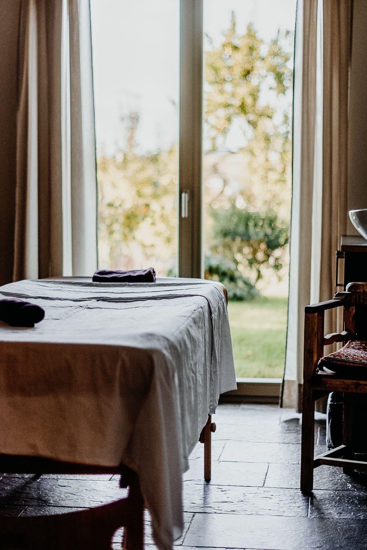 Massageliege vor Fenster mit Aussicht in den Garten