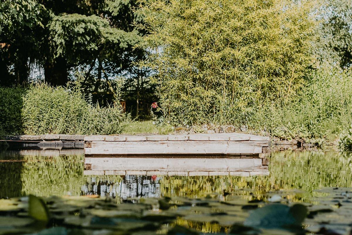 Ayurveda im Alltag: Grüner Garten mit kleinem Teich und Holzsteg