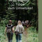 Rückansicht von zwei Frauen die auf einem Waldweg laufen.