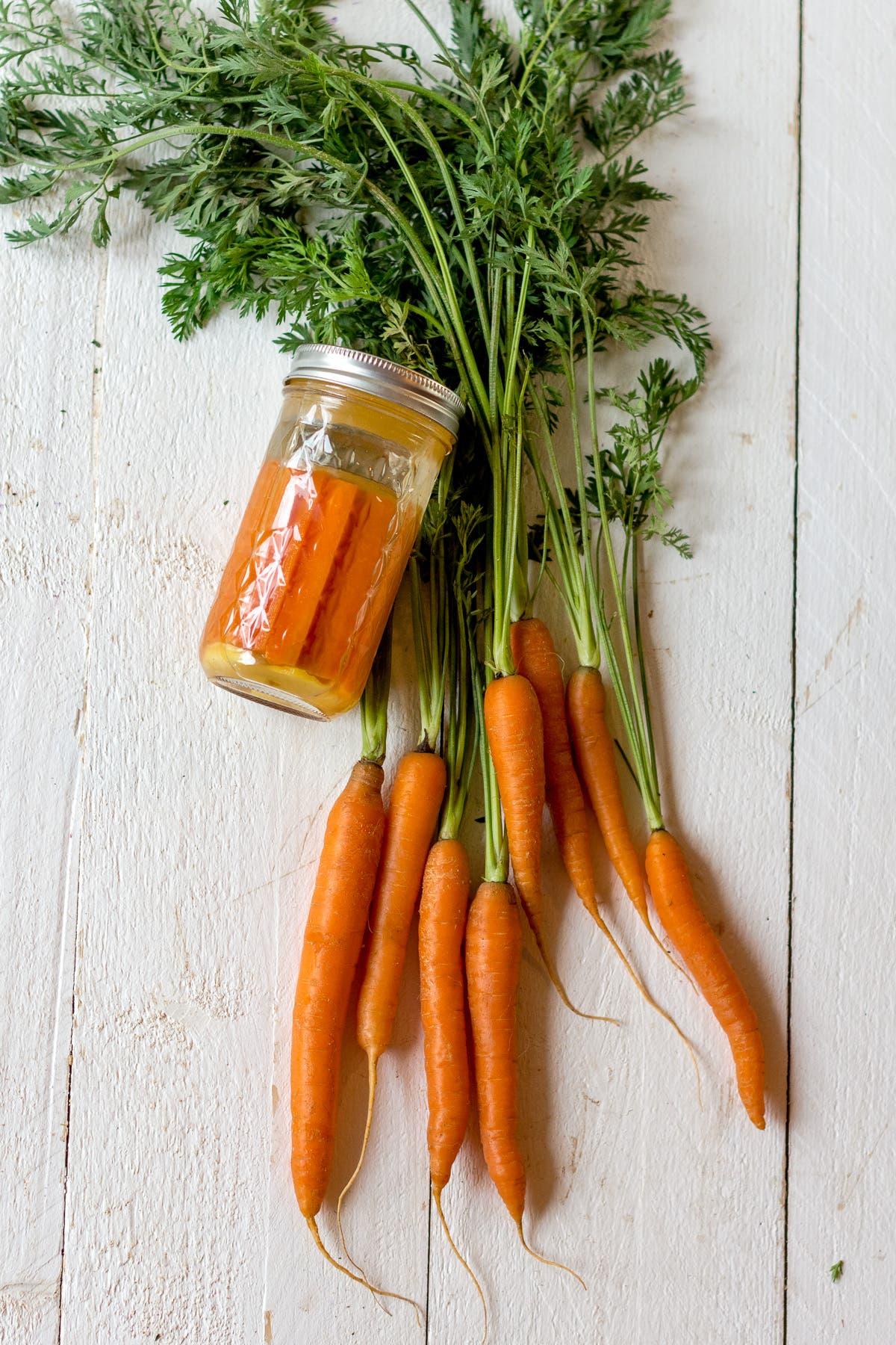 Topshot von Schraubglas neben Karottenbund, gefüllt mit fermentierten Karotten auf weißem Holzuntergrund