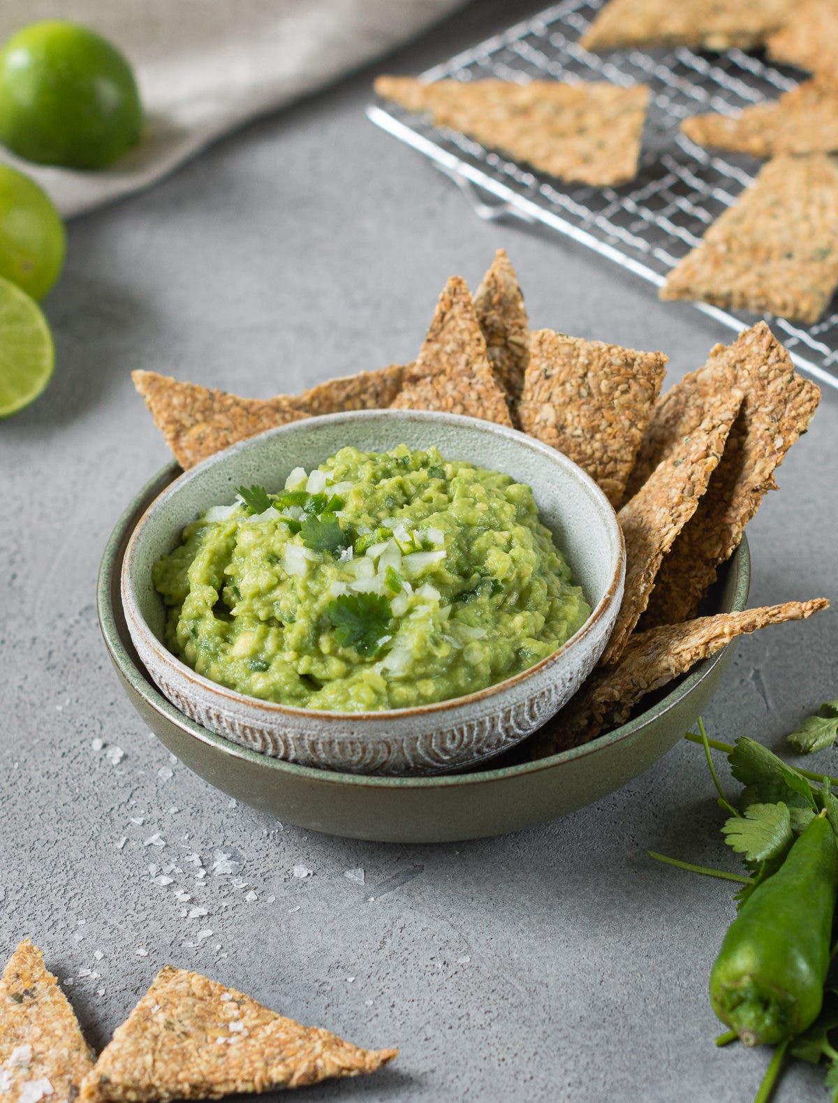 Guacamole Rezept für eine Schüssel gefüllt mit frischer Guacamole und salzigen Crackern