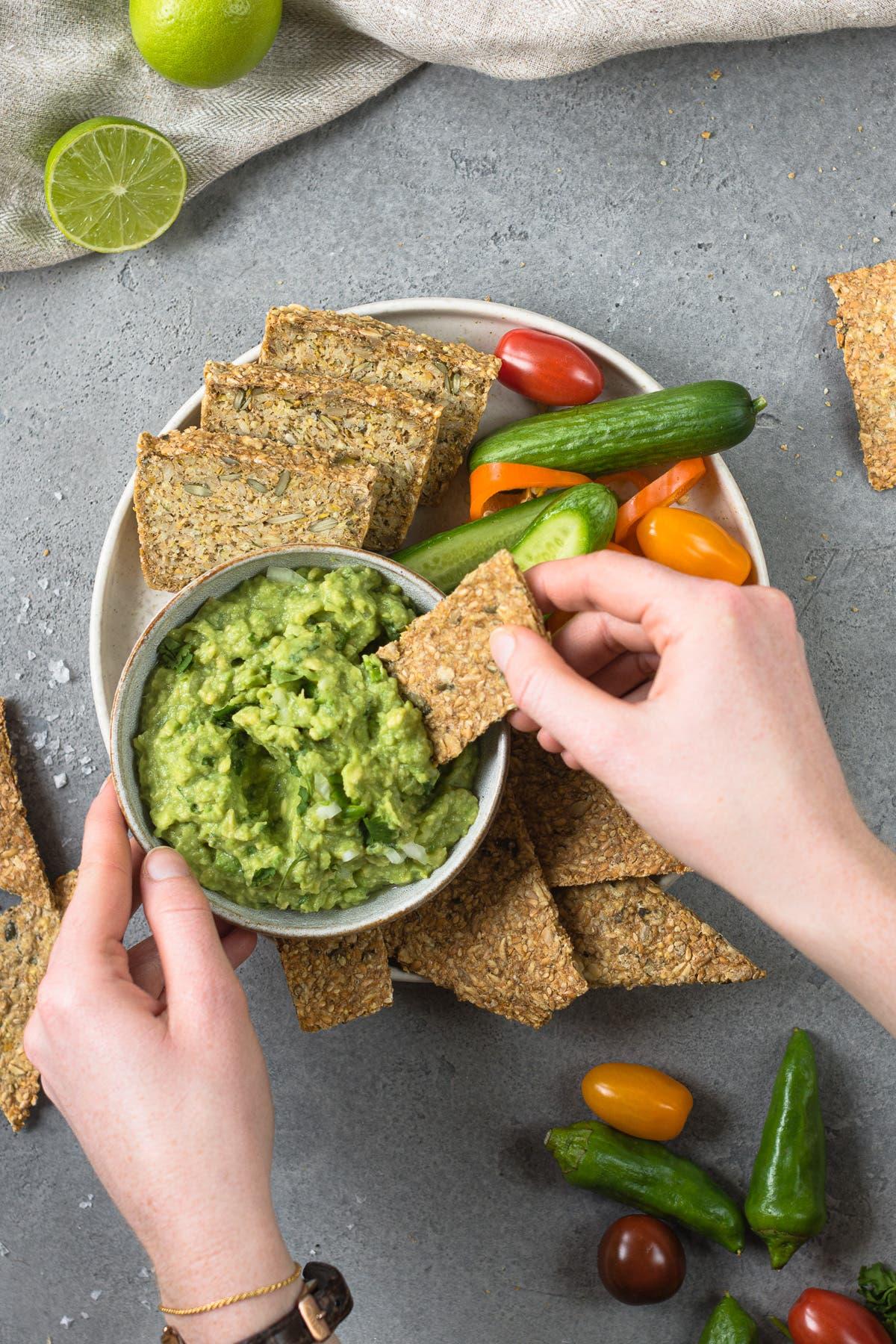 Teller mit Brot und Gemüse und eine Hand die mit einem Cracker in Guacamole dippt.