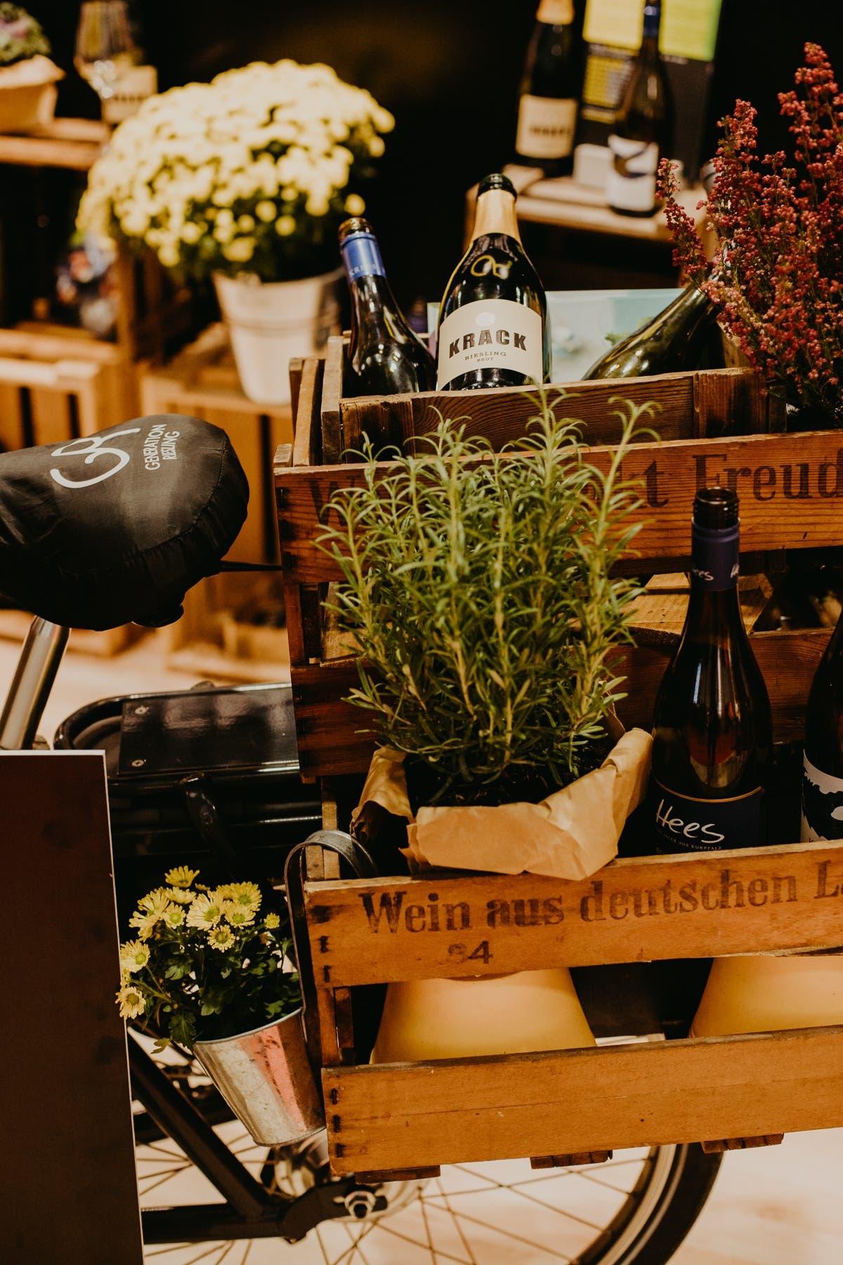 Fahrrad mit Weinkiste, Weinflasche und Rosmarin auf dem Gepäckträger.