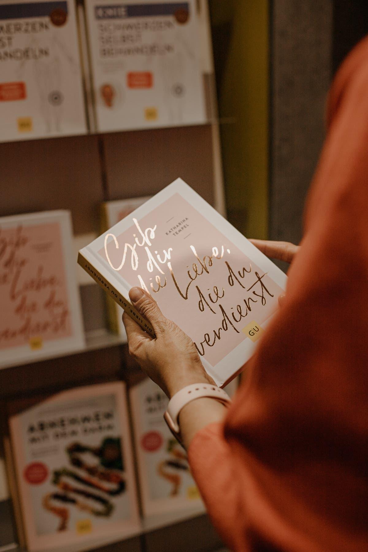 Frau hält Buch über Selbstliebe in den Händen.