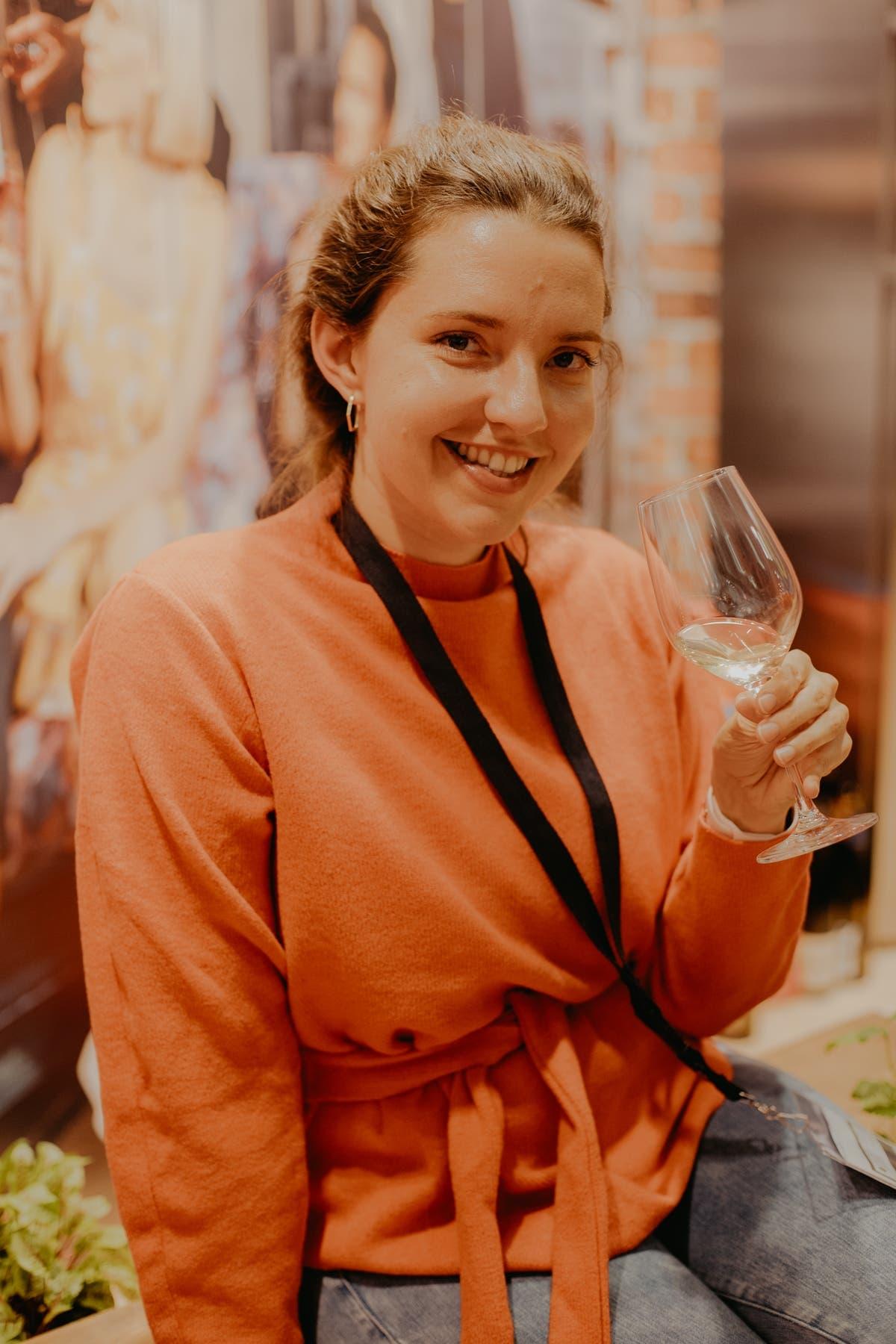 Frau schaut lächelnd in die Kamera und hat ein Weinglas in der Hand.