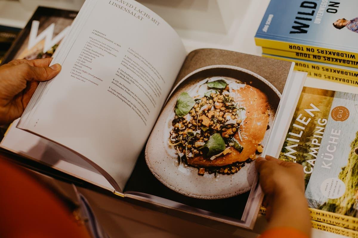 Person blättert in einem kulinarischen Kochbuch.