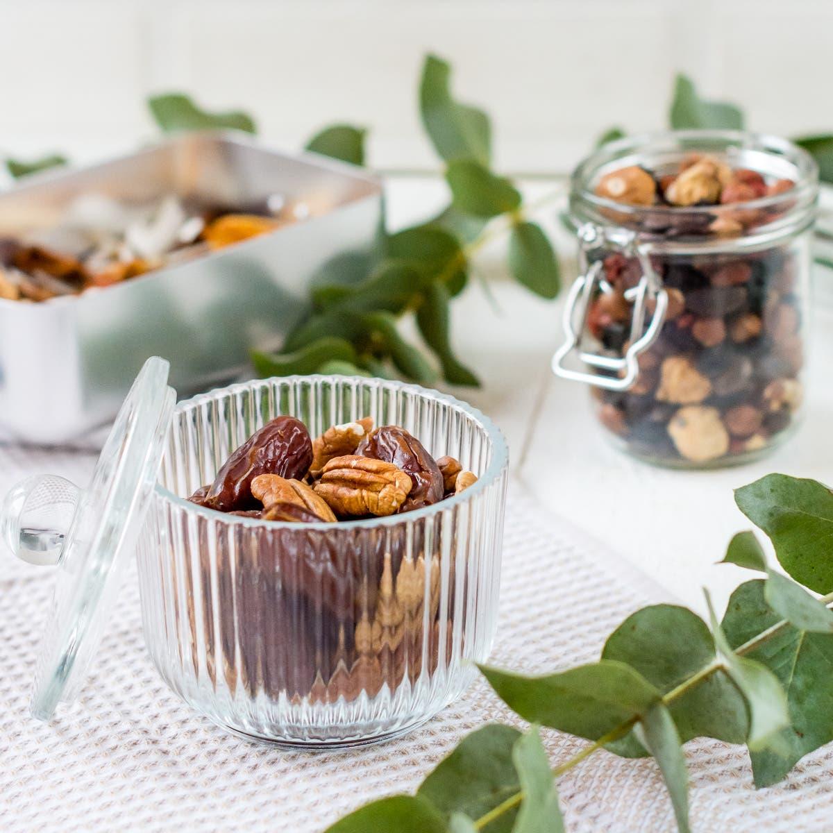 Glasschale mit Datteln und Pekannüssen.