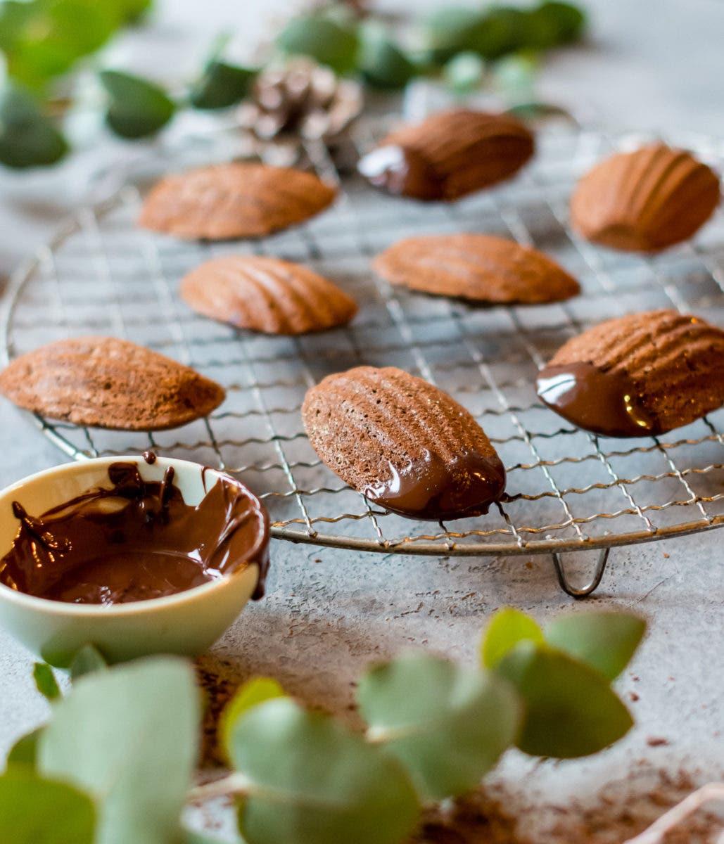 Schokoladenmadeleines auf einem Kuchengitter und eine kleine Schale mit geschmolzener Schokolade.